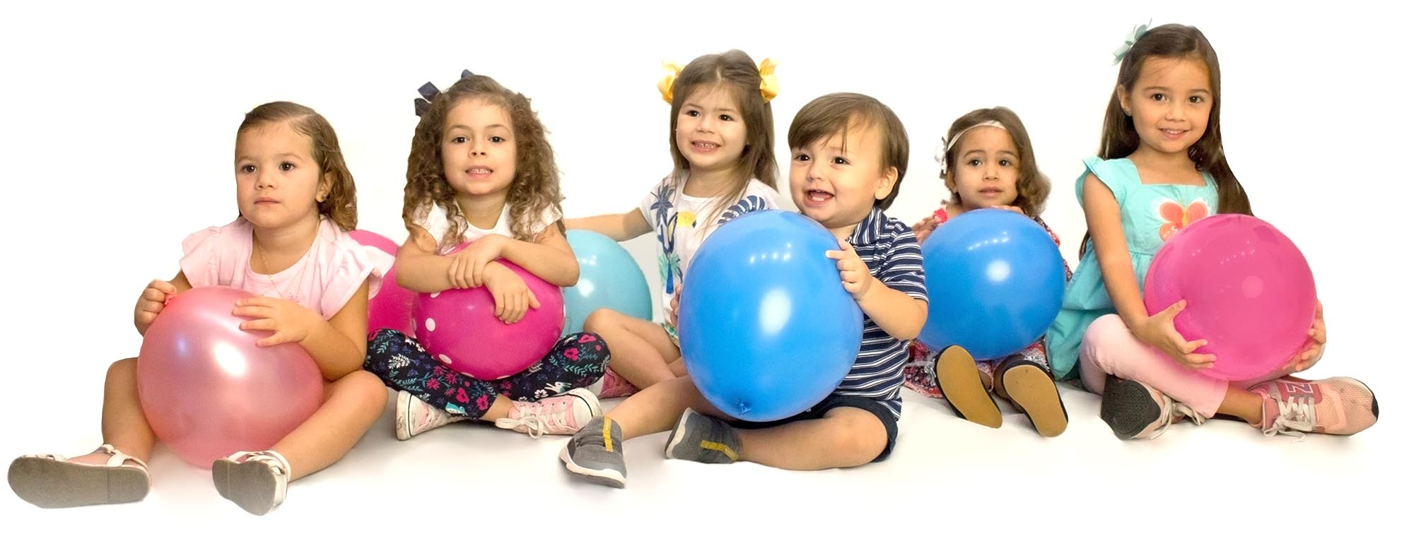 Little kids holding balloons